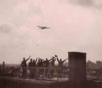 Waving at a Lancaster from a rooftop