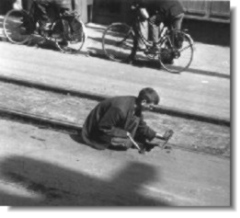 Young Dutch boy steeling the wood block from the tram rails in order to get wood, Photo, national archives of canada